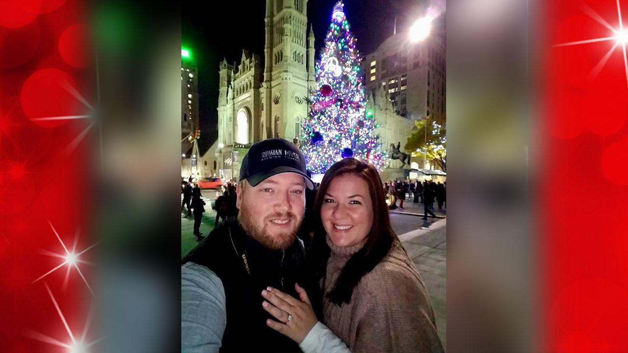Leslie Walter and her fiance, Mike Long, take a photo in front of the Christmas tree at City Hall.