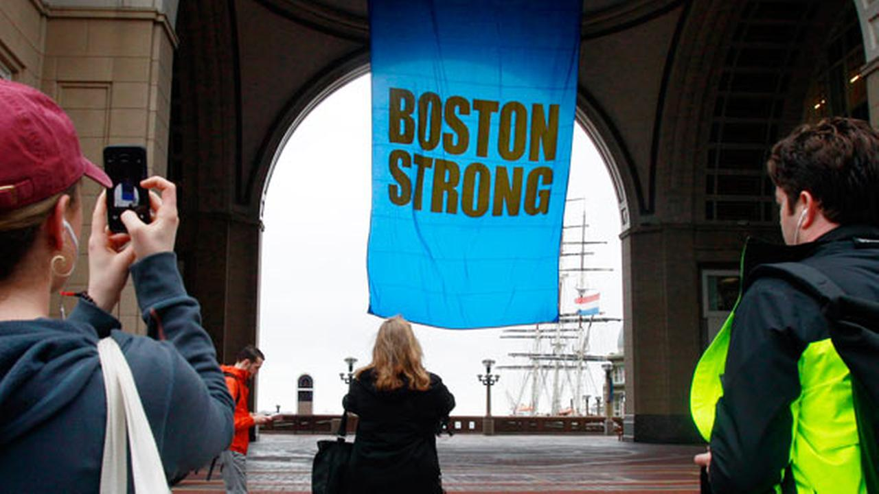 People photograph a banner reading Boston Strong as it hangs at Rowes Wharf on the first anniversary of the Boston Marathon bombings, Tuesday, April 15, 2014, in Boston. (AP Photo/Bill Sikes)