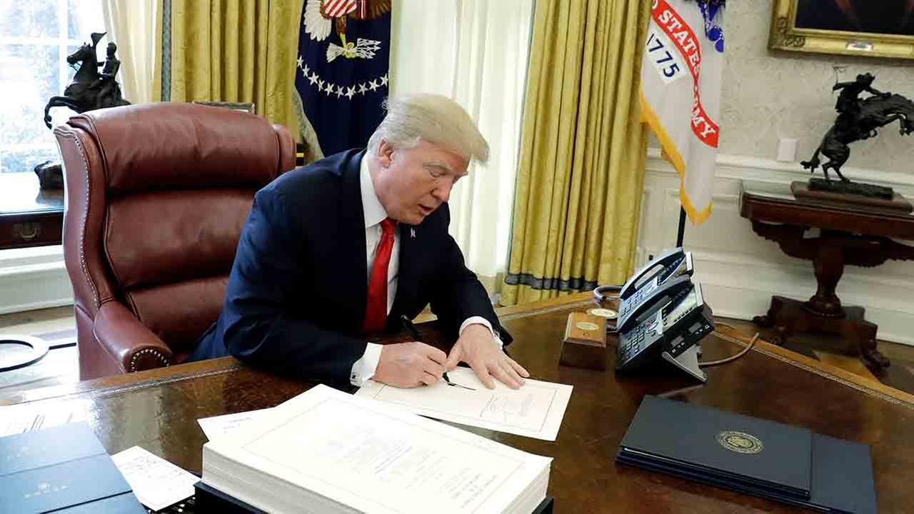President Donald Trump signs into law a $1.5 trillion tax overhaul package, Friday, Dec. 22, 2017, in the Oval Office of the White House in Washington.