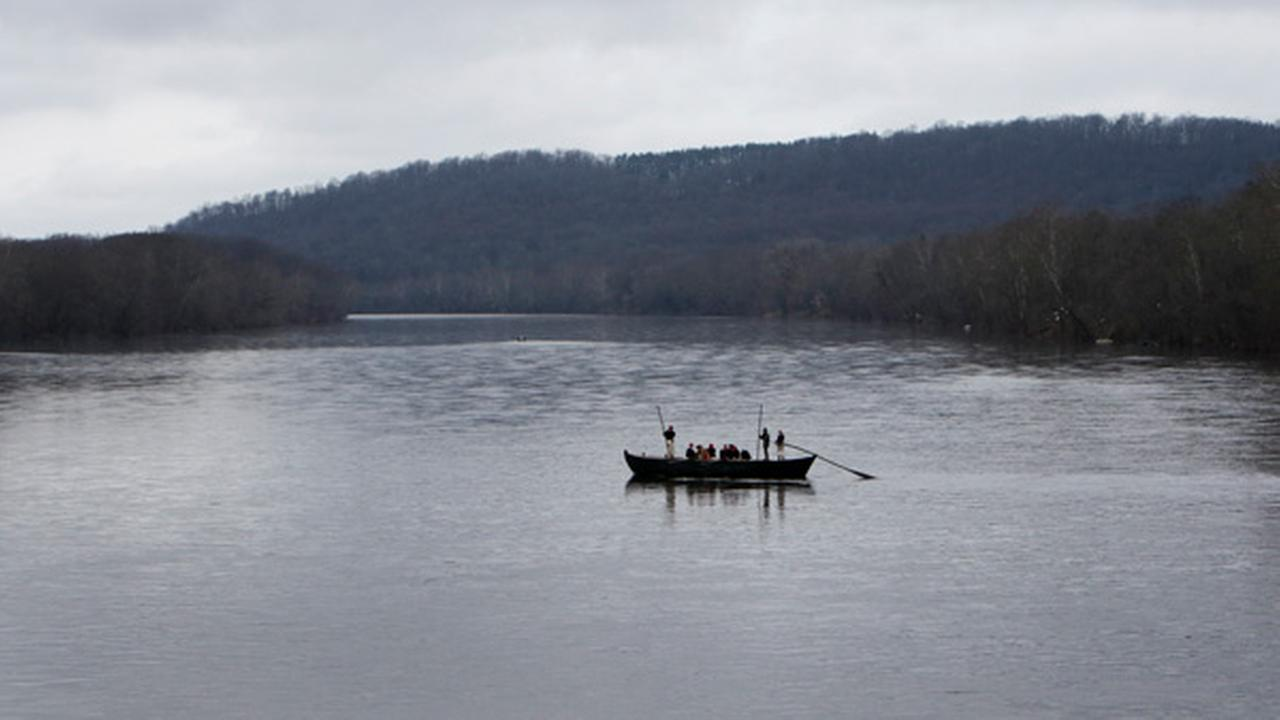 In this Dec. 25, 2015 photo, a group of Revolutionary War re-enactors row a Durham boat during the re-enactment of Washington crossing the Delaware River, in Washington Crossing.
