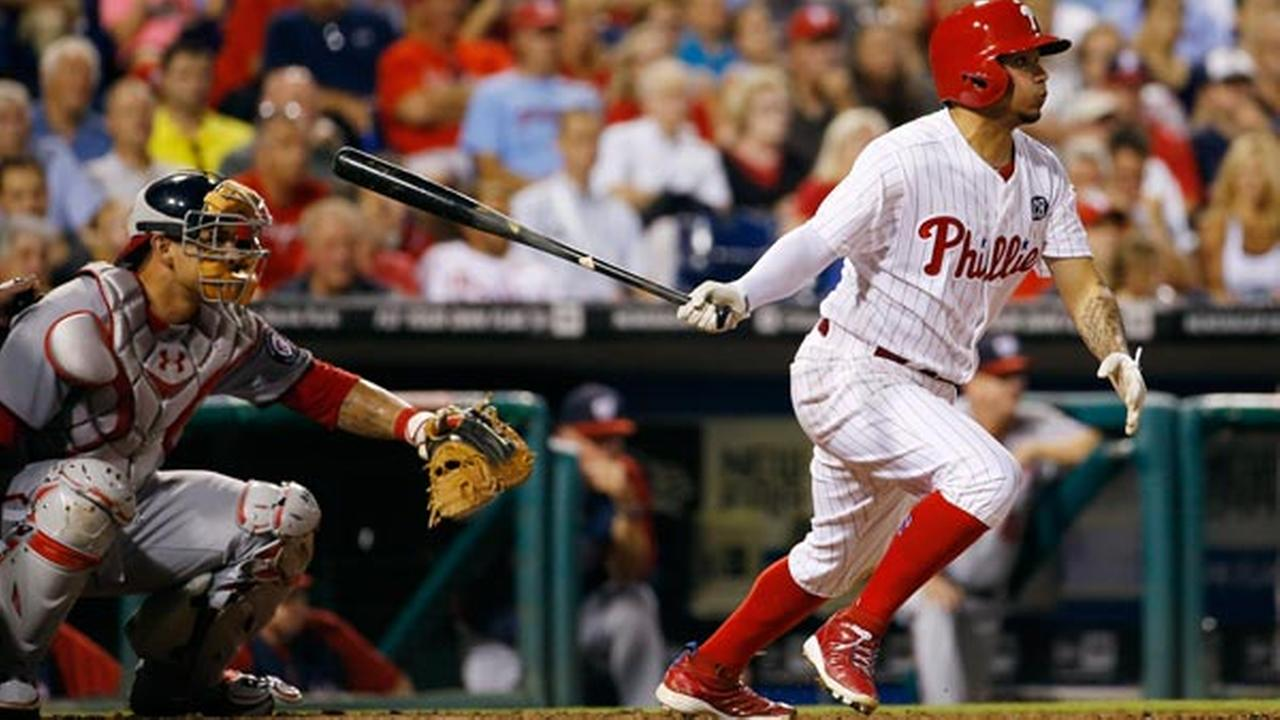 Philadelphia Phillies Freddy Galvis, right, follows through after hitting a single off Washington Nationals relief pitcher Drew Storen during the seventh inning of a baseball game