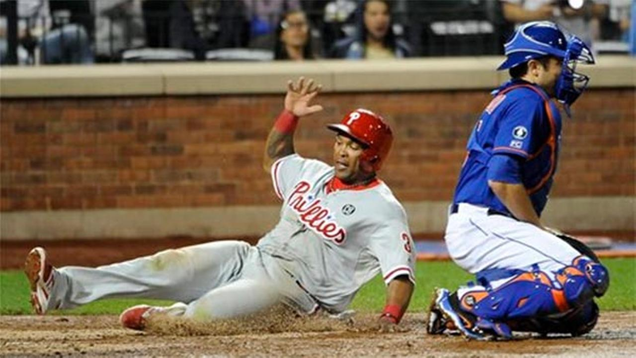 Philadelphia Phillies Marlon Byrd, left, scores at home plate behind New York Mets catcher Travis dArnaud at Citi Field, Friday, Aug. 29, 2014.
