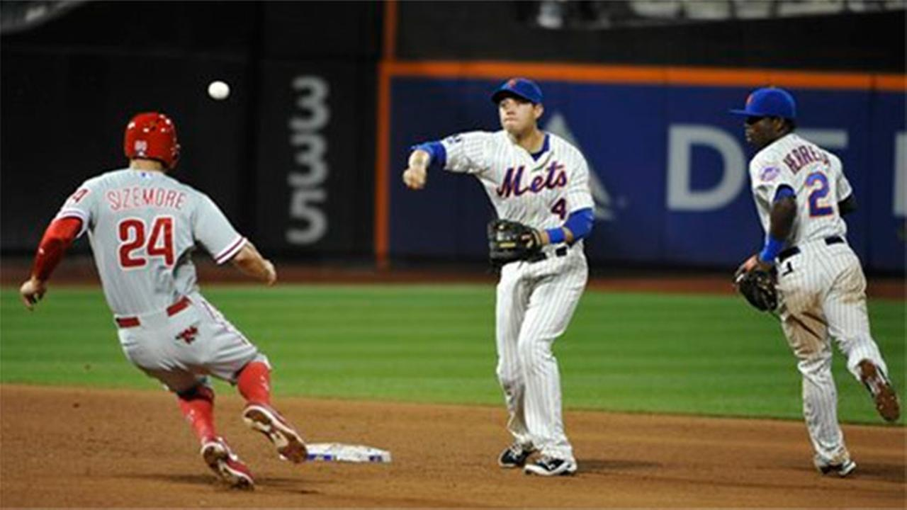 New York Mets second baseman Dilson Herrara (2) watches as shortstop Wilmer Flores (4) throws to first base to complete a double play at Citi Field on Saturday, Aug. 30, 2014.