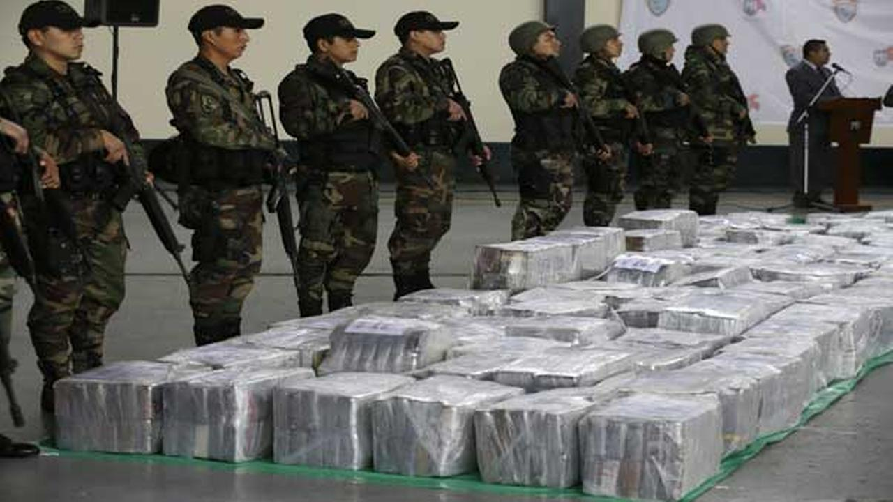 Police stand guard over seized cocaine as they present it to the press at a police base in Lima, Peru, Monday, Sept. 1, 2014.