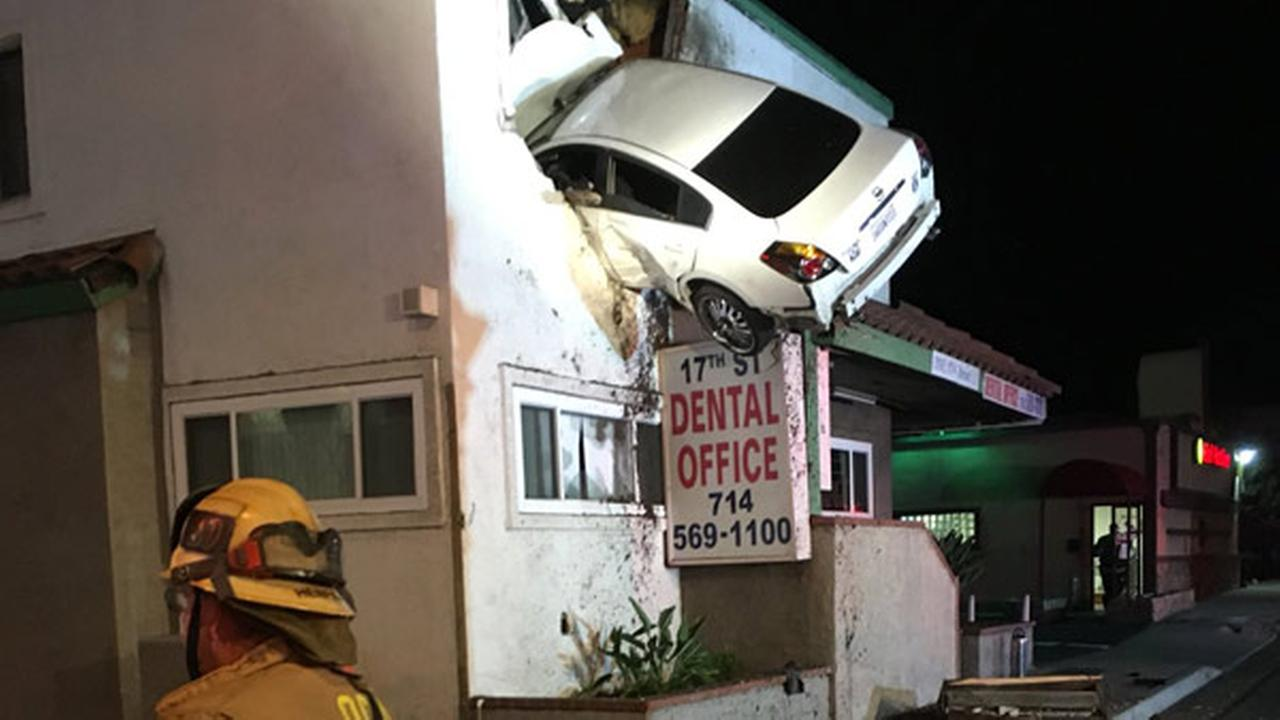 A firefighter is seen near an office building in Santa Ana after a car slammed into the structures second floor in a bizarre crash on Sunday, Jan. 14, 2018.