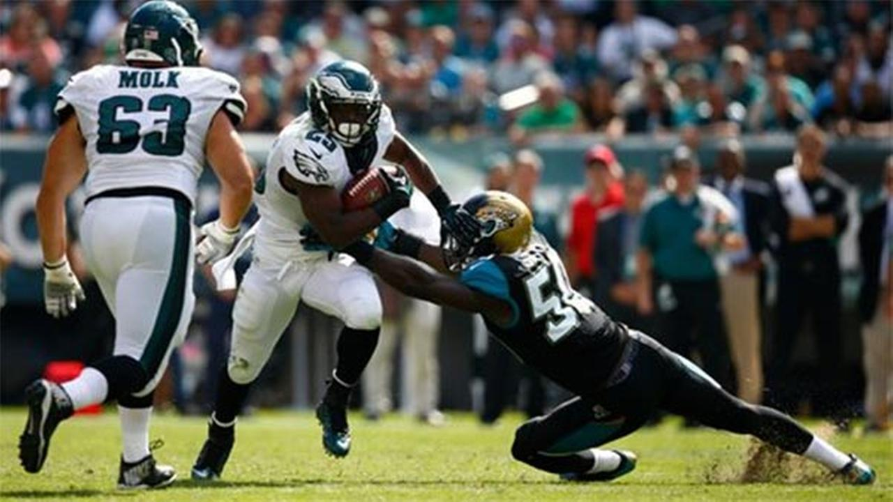 Philadelphia Eagles LeSean McCoy, center, tries to break a tackle by Jacksonville Jaguars Telvin Smith, Sunday, Sept. 7, 2014, in Philadelphia.