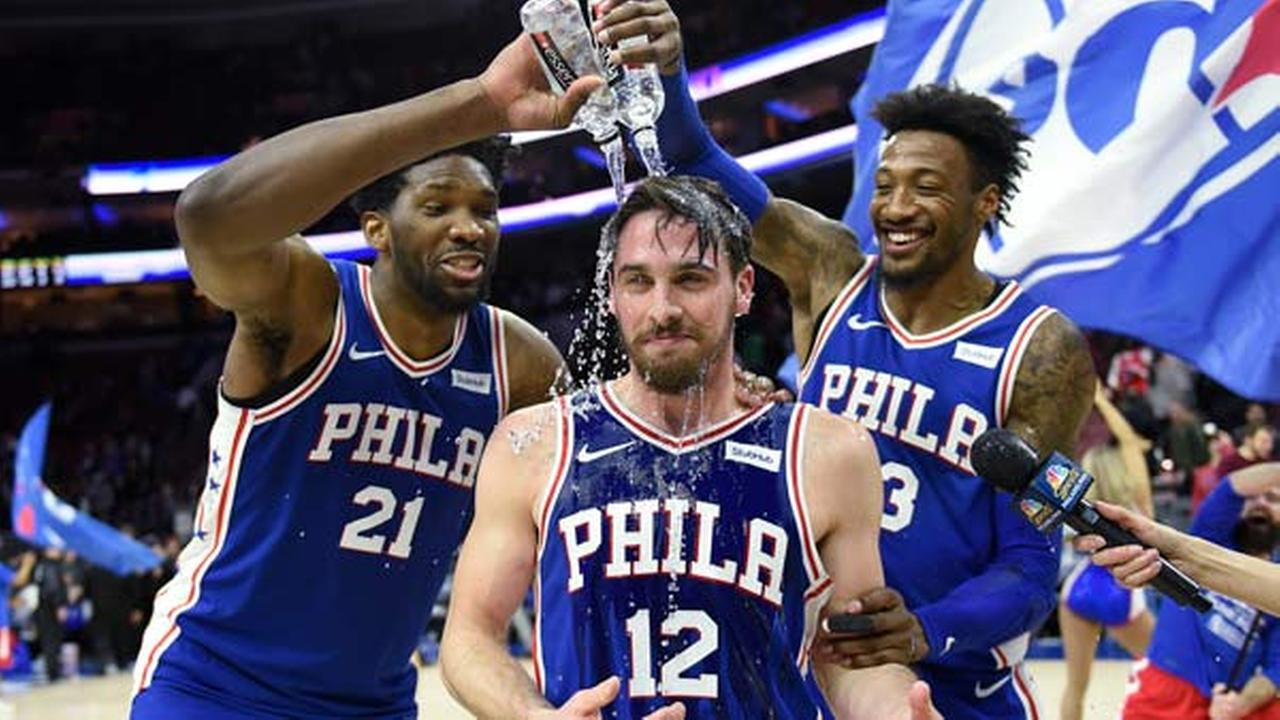 Philadelphia 76ers T.J. McConnell (12) is doused with water by Robert Covington and Joel Embiid at the end of an NBA basketball game against the New York Knicks, Feb 12, 2018.