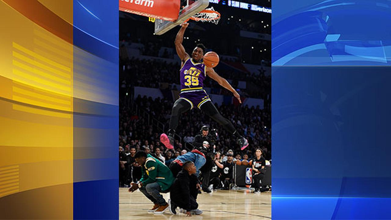 Utah Jazzs Donovan Mitchell, top, dunks over three people, including actor Kevin Hart, left, during the NBA All-Star basketball Slam Dunk contest, Saturday, Feb. 17, 2018.