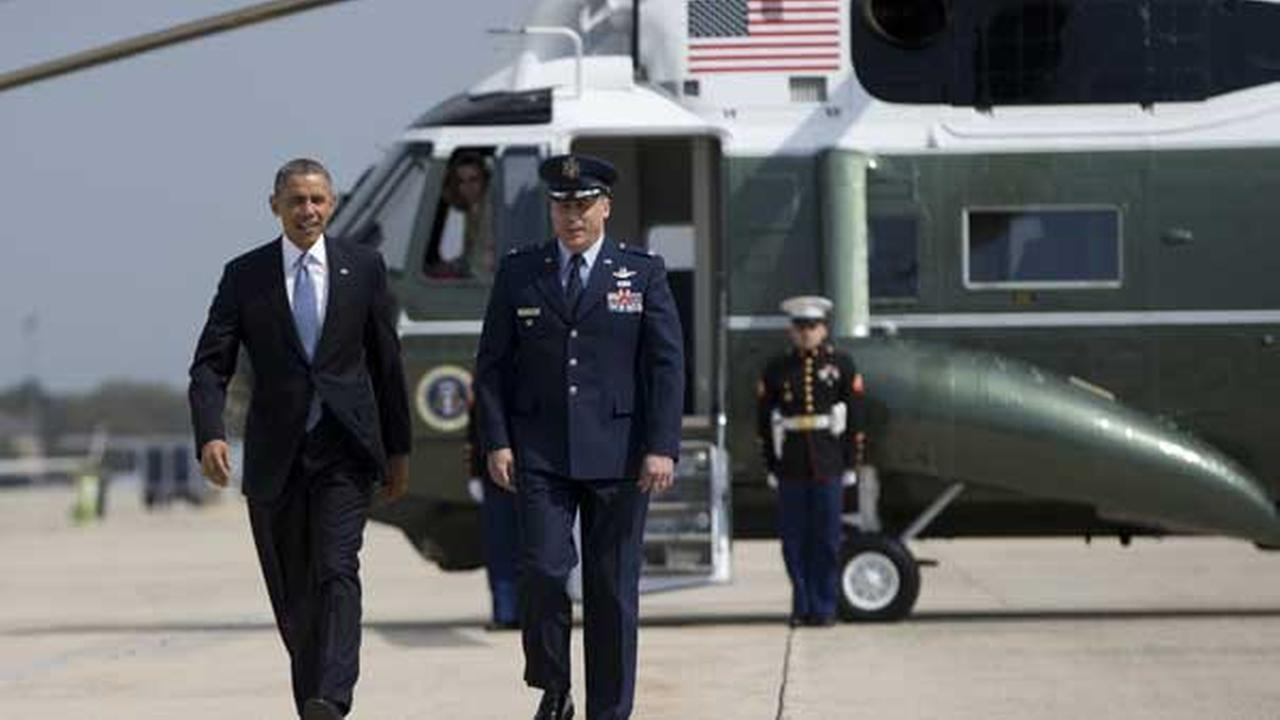 President Barack Obama walks from the Marine One helicopter with Col. Preston Williamson, vice commander, 89th Airlift Wing, Andrews Air Force Base, Md.,to board of Air Force One, Tuesday, April 22, 2014, at Andrews Air Force Base, Md, en route to Oso, Wash., the site of the deadly mudslide that struck the community.