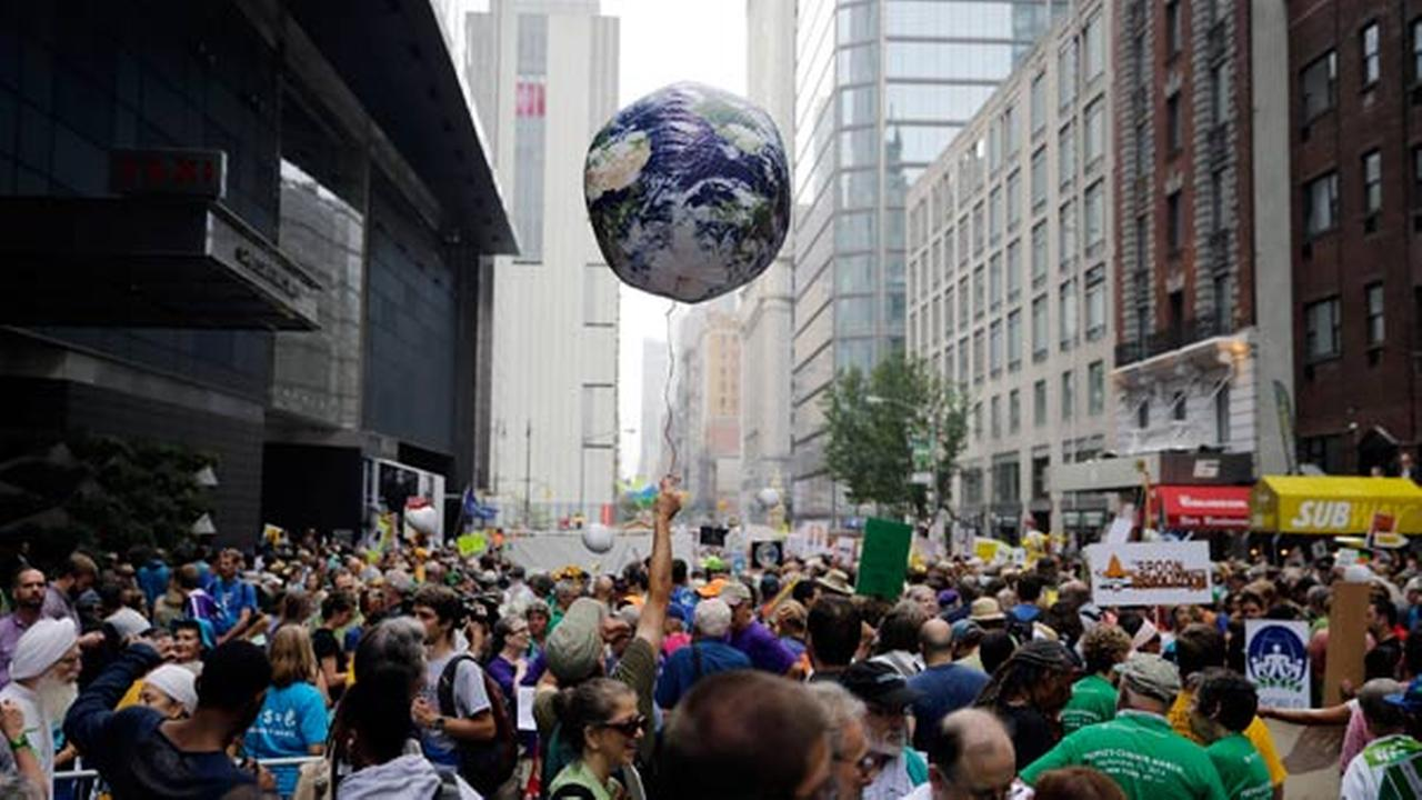 A man throws an earth balloon into the air as people fill 58th Street between 8th and 9th Avenue before a global warming march in New York Sunday, Sept. 21, 2014.