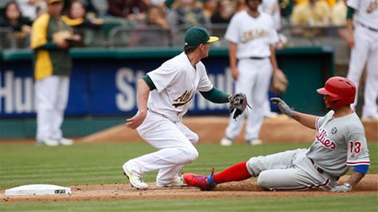 Philadelphia Phillies Freddy Galvis (13) slides into third past Oakland Athletics third baseman Josh Donaldson for a triple in the sixth inning, Sunday, Sept. 21, 2014.