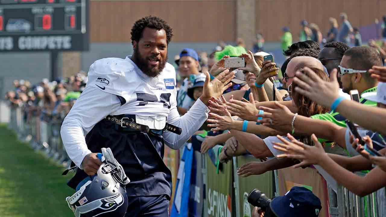 Seattle Seahawks Michael Bennett greets fans as he heads to the practice field during NFL football training camp Friday, Aug. 4, 2017, in Renton, Wash.