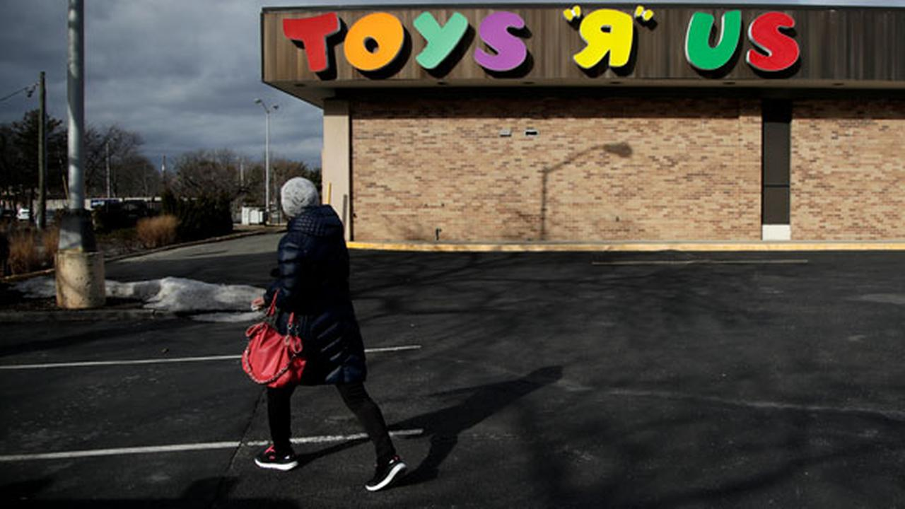 A woman walks in a parking lot of a Toys R Us store, Wednesday, Jan. 24, 2018, in Wayne, N.J.