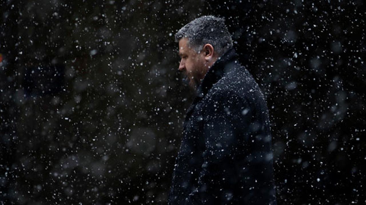 A man walks through falling snow Tuesday, March 20, 2018, in Philadelphia.