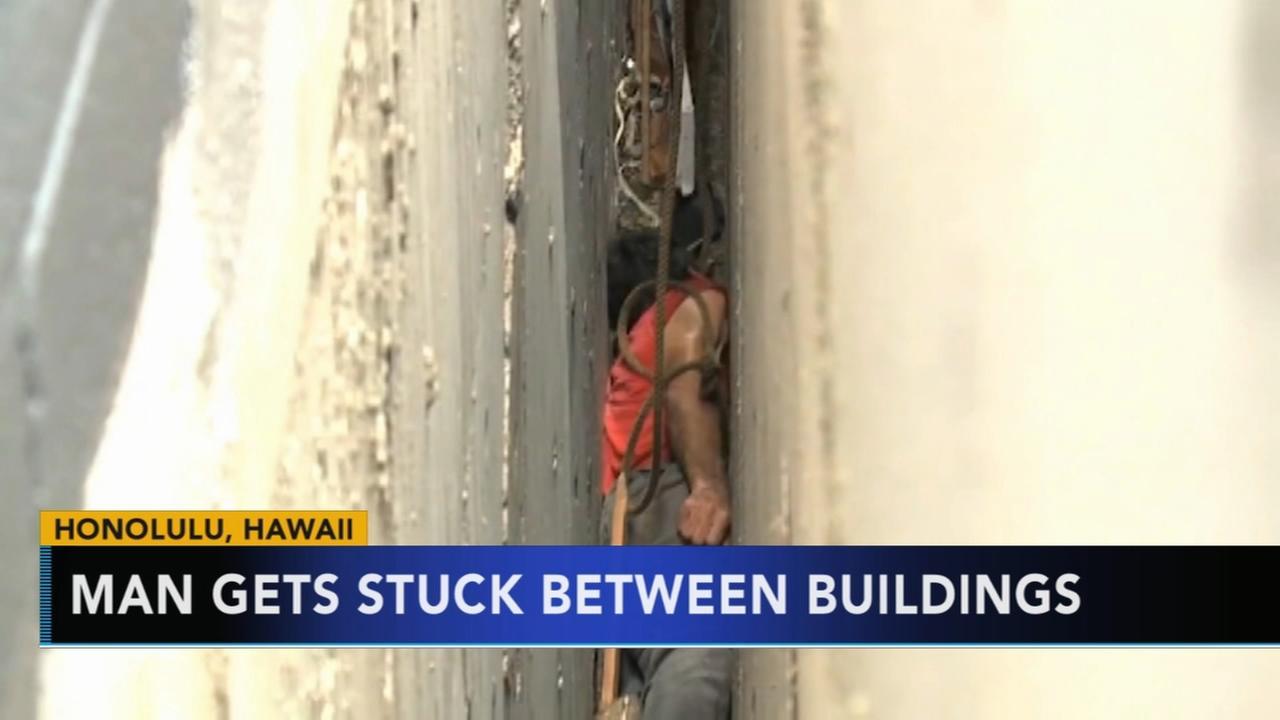 Man gets stuck between buildings