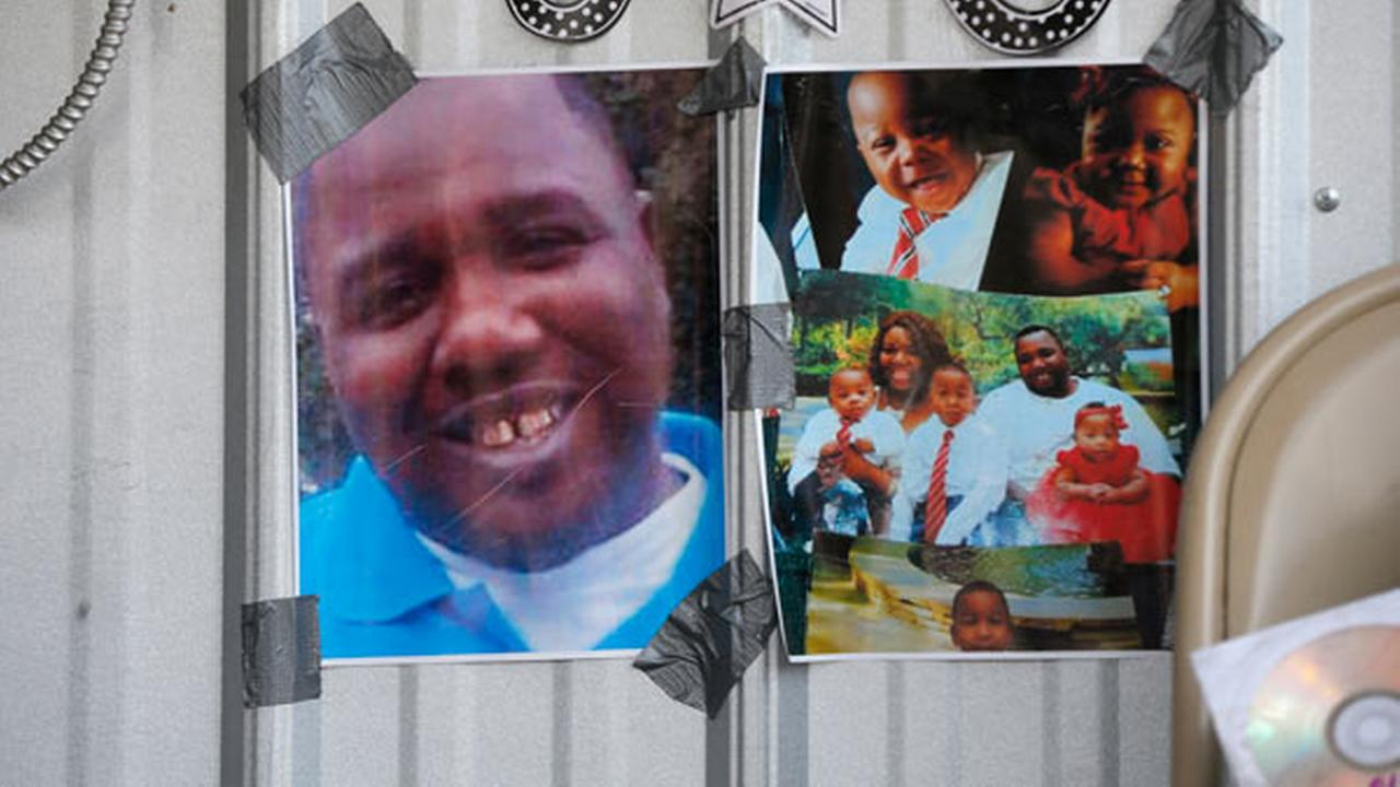 FILE - In this July 6, 2016 file photo, photos of Alton Sterling are taped to the wall at a makeshift memorial outside the Triple S convenience store in Baton Rouge, La.