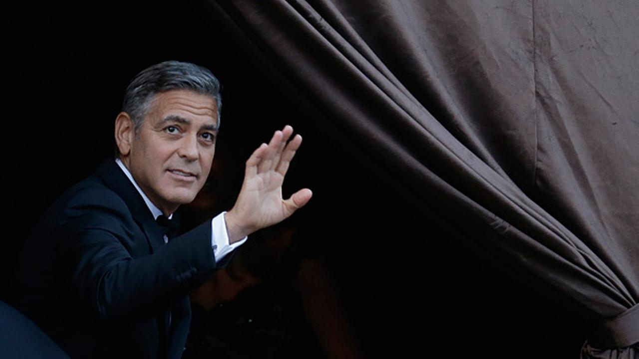 George Clooney waves as he arrives at the Amam Luxury Hotel for his marriage with Amal Alamuddin in Venice, Italy, Saturday, Sept. 27, 2014.(AP Photo/Luca Bruno)