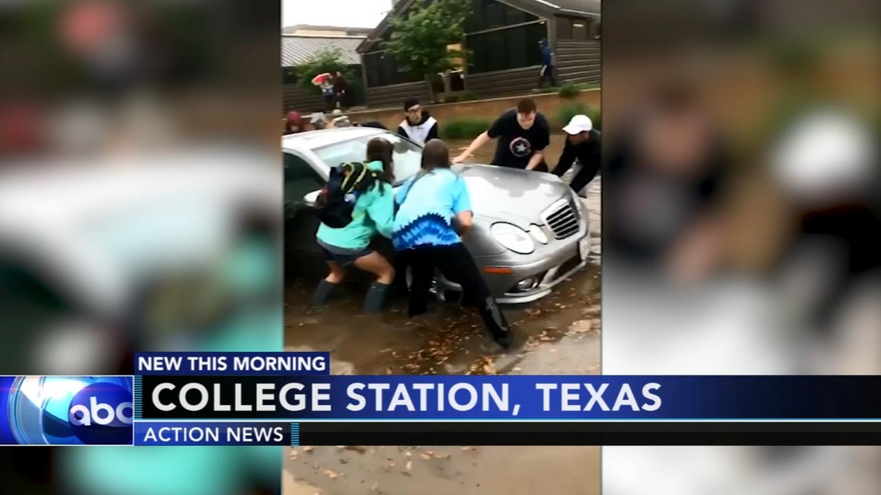 Group of strangers help stuck car on flooded roadway