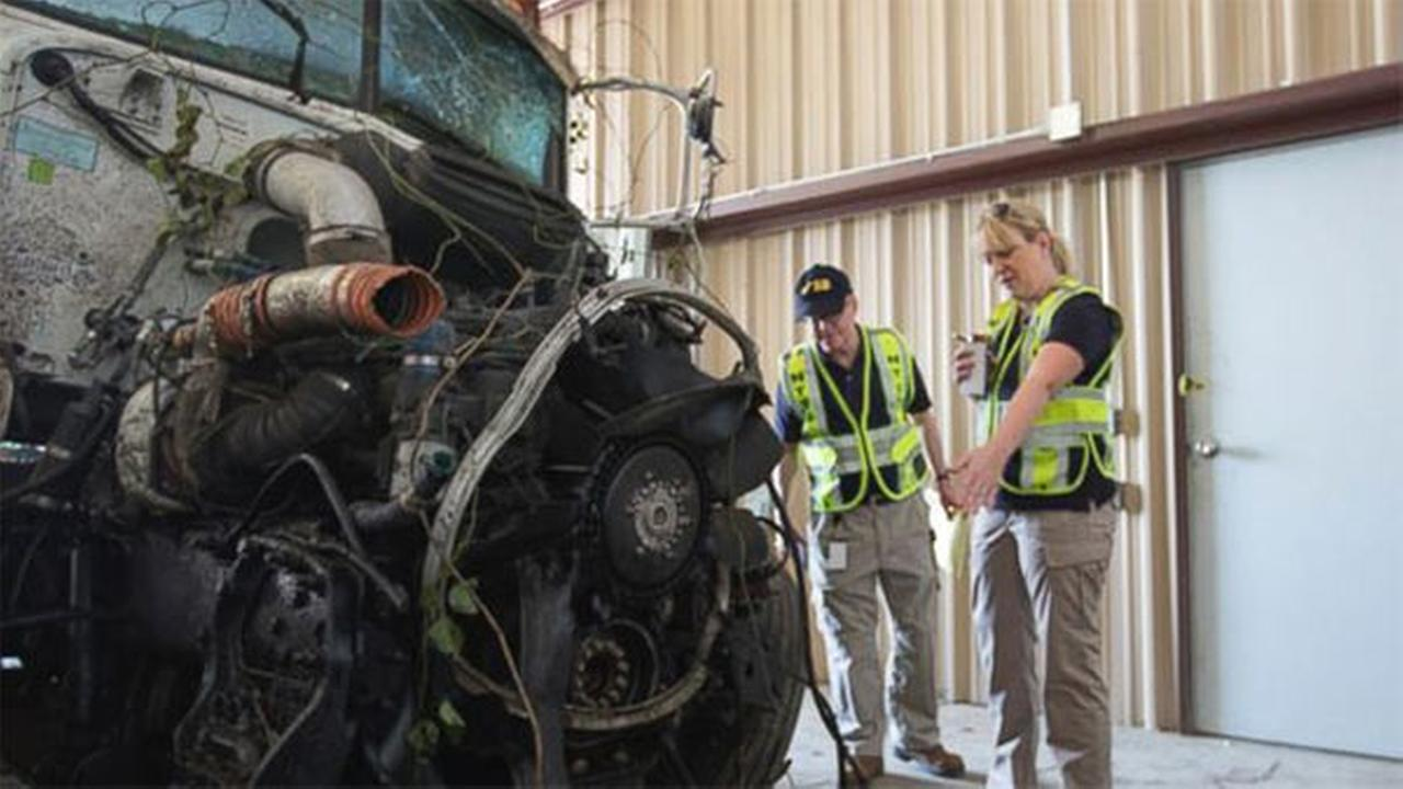 In this photo provided by The National Transportation Safety Board, officials examine part of the wreckage involved in a fatal highway accident in Davis, Okla.