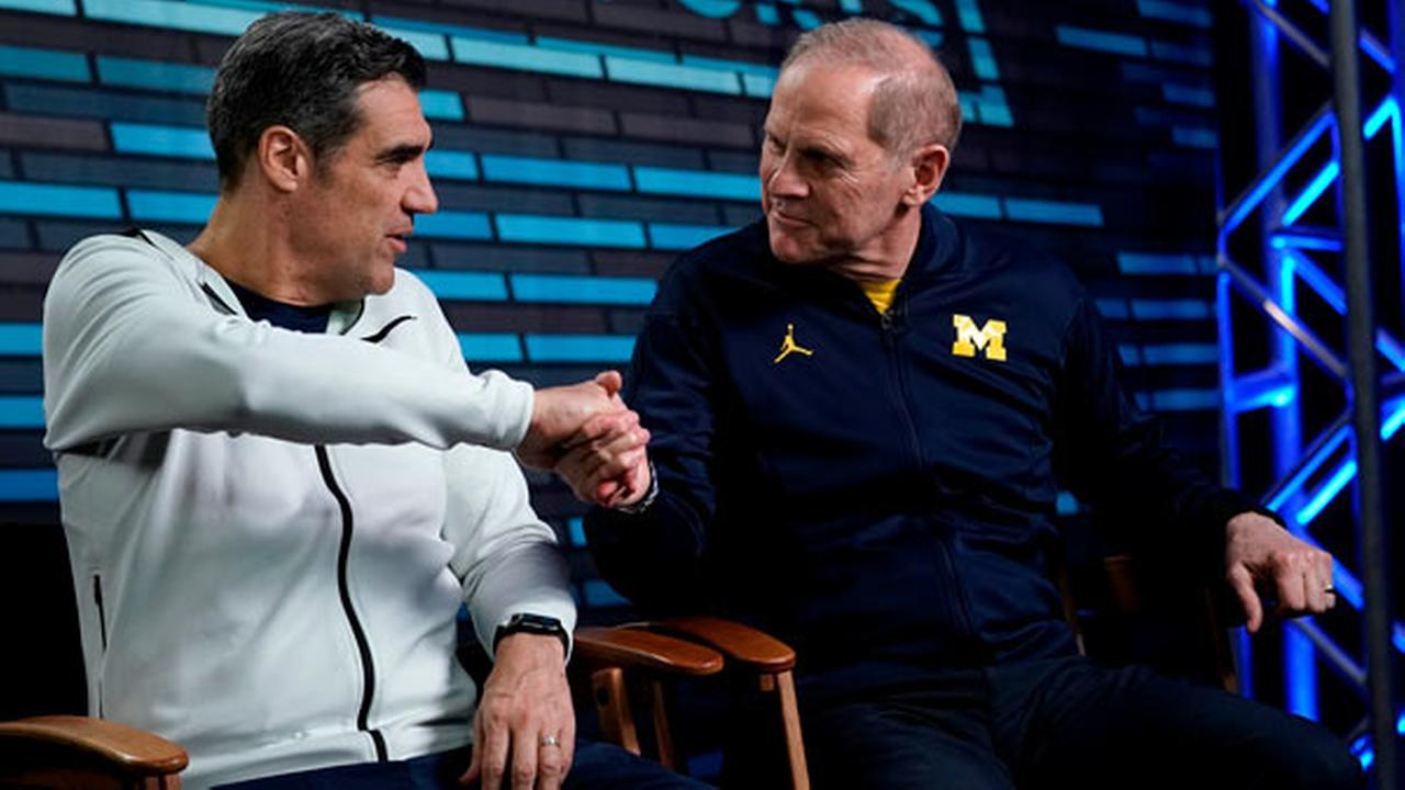 Villanova head coach Jay Wright, left, and Michigan head coach John Beilein shake hands during an interview for CBS Sports Network.