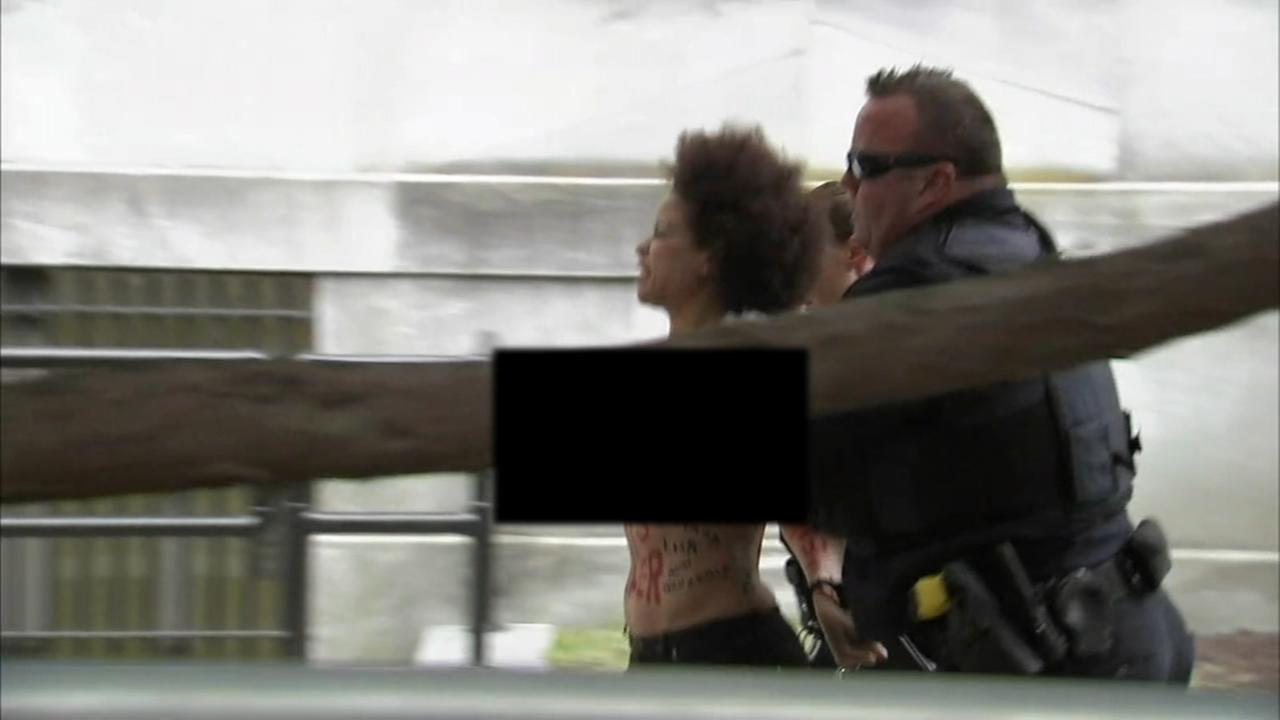 Topless protester taken into custody at Cosby trial