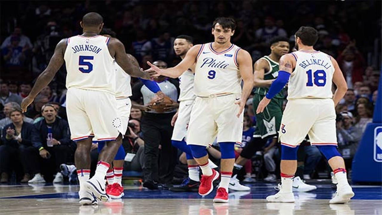 Philadelphia 76ers Dario Saric, center, celebrates with Marco Belinelli, right, and Amir Johnson, left, during the first half of an NBA basketball game against the Milwaukee Bucks