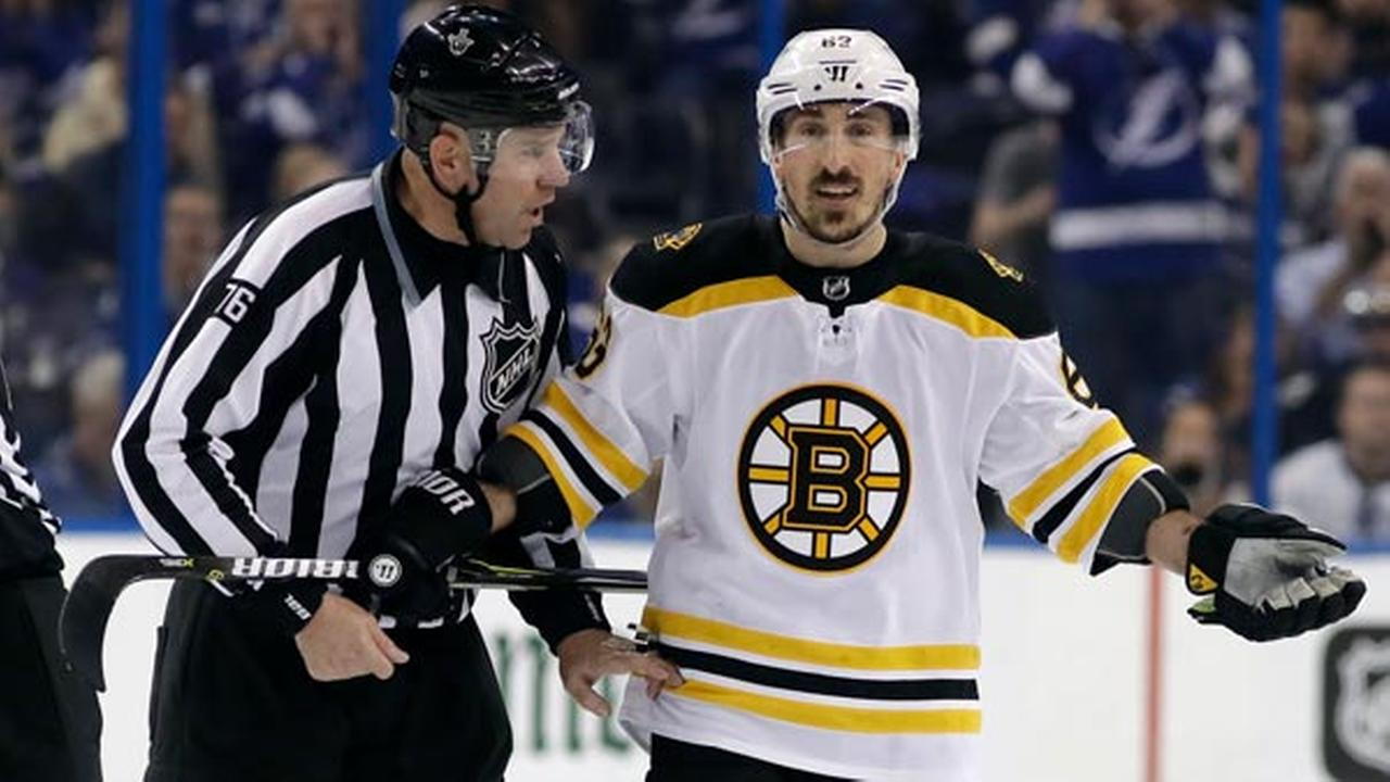 Boston Bruins left wing Brad Marchand (63) is escorted off the ice by linesman Michel Cormier (76) after taking a penalty against the Tampa Bay Lightning.