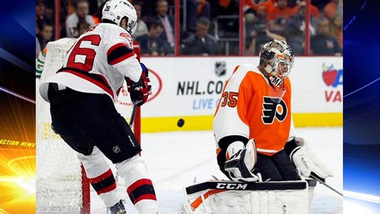 The puck goes past Philadelphia Flyers goalie Steve Mason, right, but not into the net as New Jersey Devils Patrick Elias, left, watches, Oct. 9, 2014, in Philadelphia