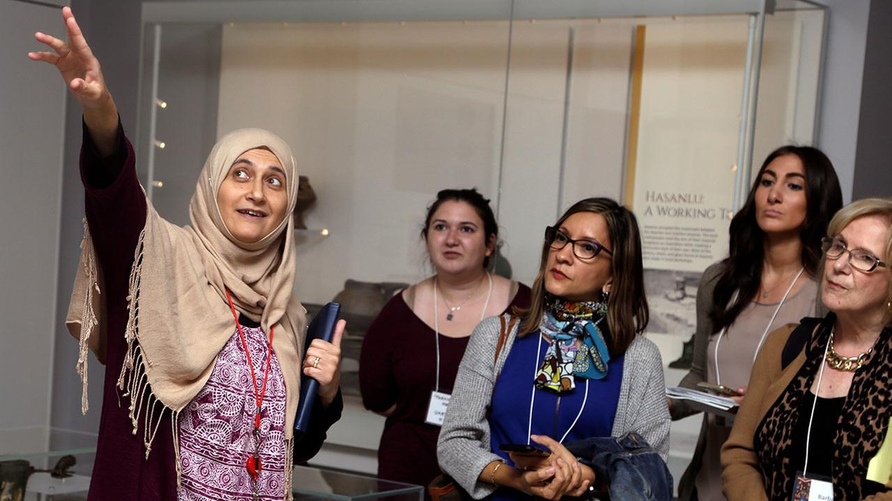 In this April 26, 2018 photo, Moumena Saradar, left, originally from Syria, guides visitors through the Middle East gallery at Penn Museum.