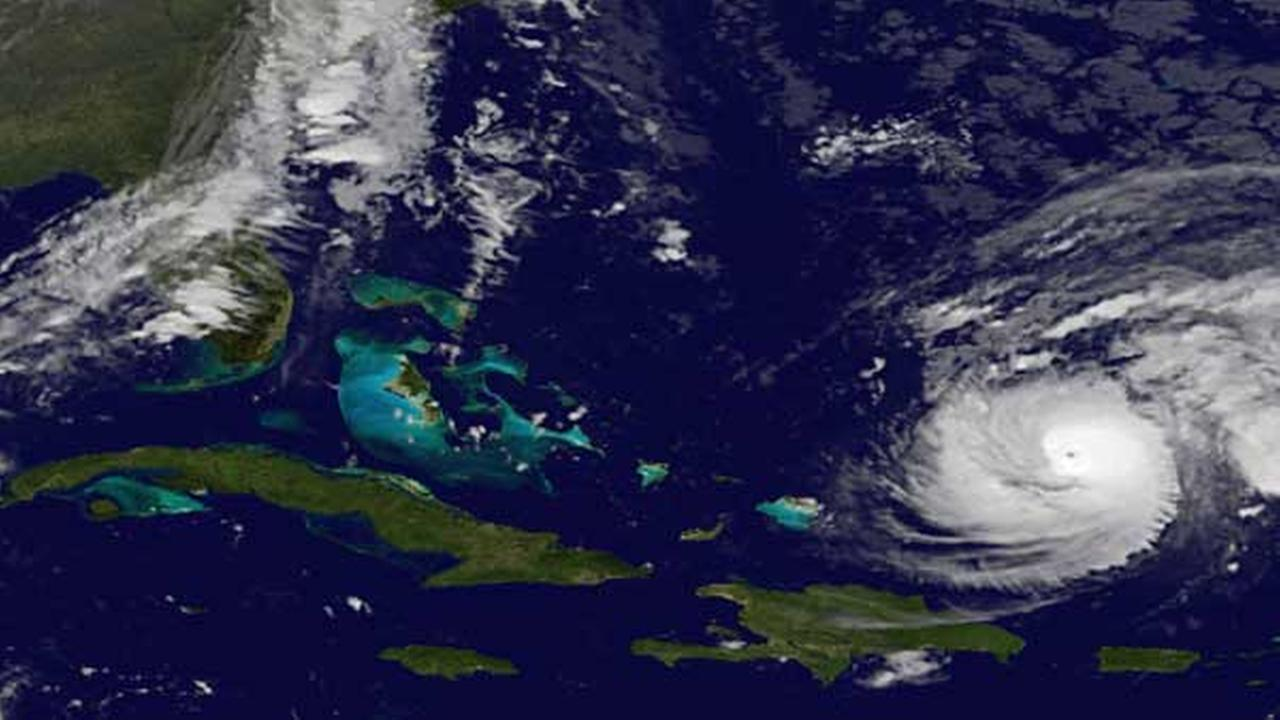 This image provided by NOAA Wednesday Oct. 15, 2014 shows Hurricane Gonzalo, lower right, which forecasters said could become a powerful category 4 storm Wednesday.