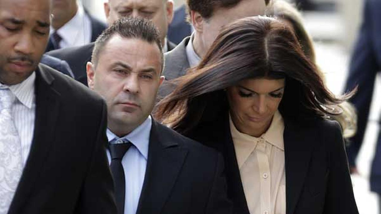 FILE - In this Oct. 2, 2014, file photo, The Real Housewives of New Jersey stars Giuseppe Joe Giudice, center, and his wife, Teresa Giudice before a court appearance.