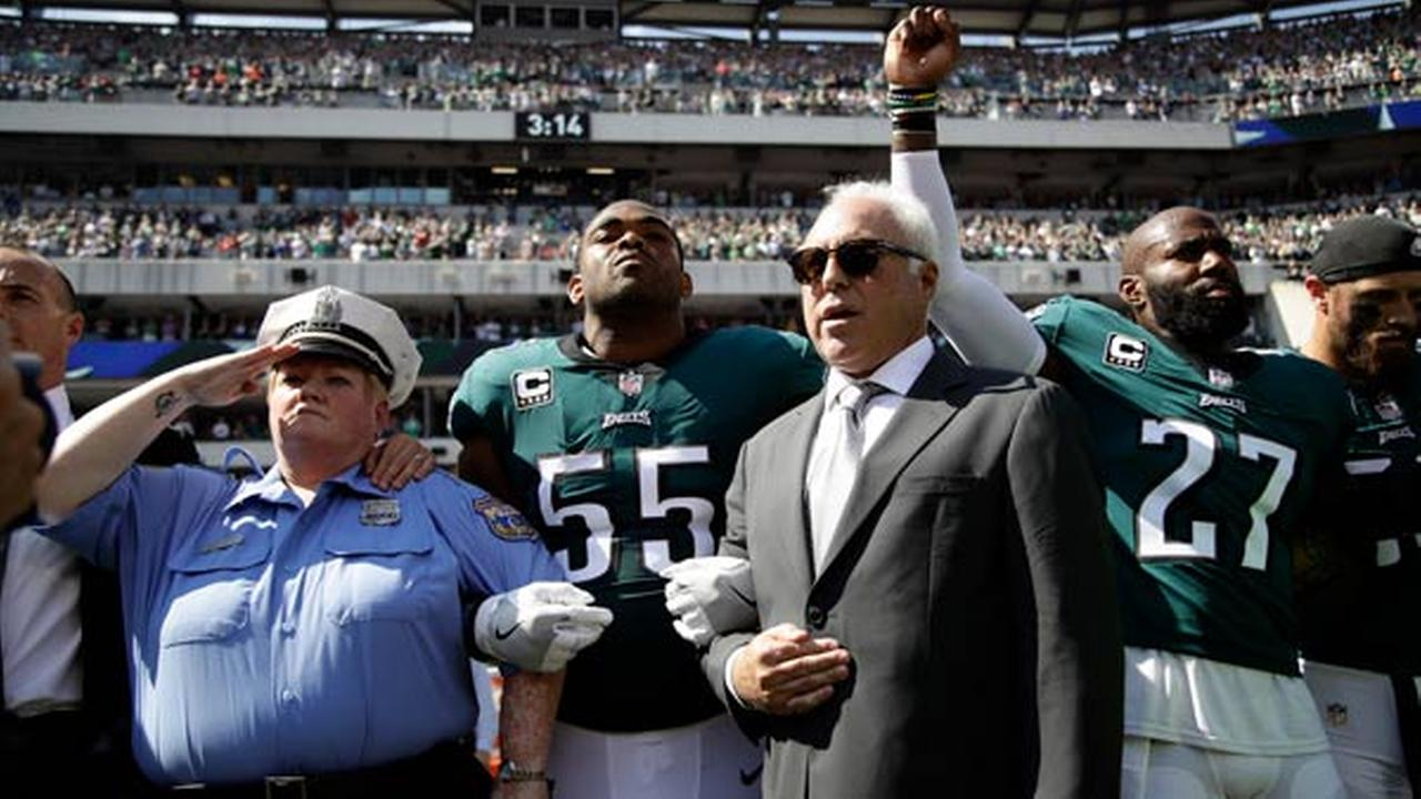 Philadelphia Eagles players, owner Jeffrey Lurie, Eagles President Don Smolenski, and a Philadelphia police officer, stand for the national anthem.