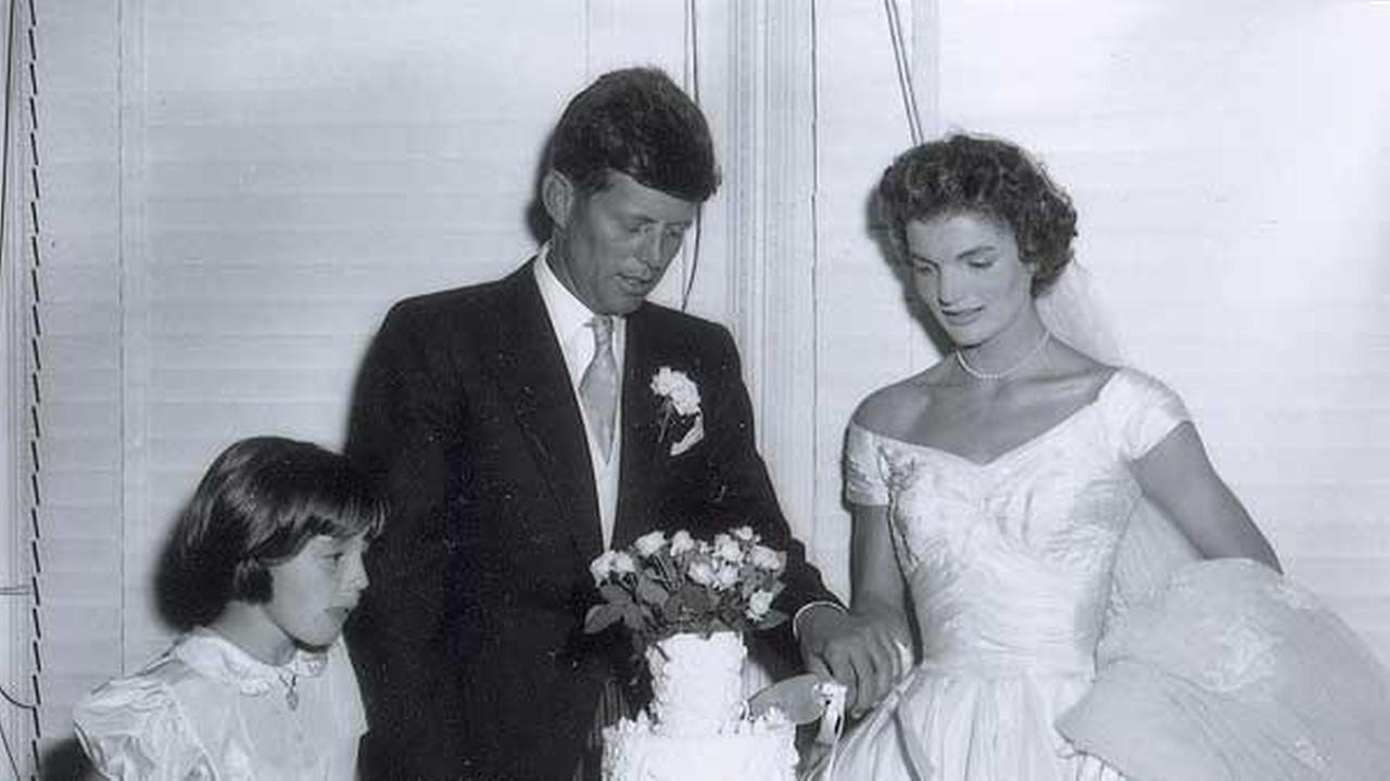 In this Sept. 12, 1953 photo released by RR Auction, John F. Kennedy and his new bride Jacqueline cut the wedding cake at their reception in Newport, R.I.
