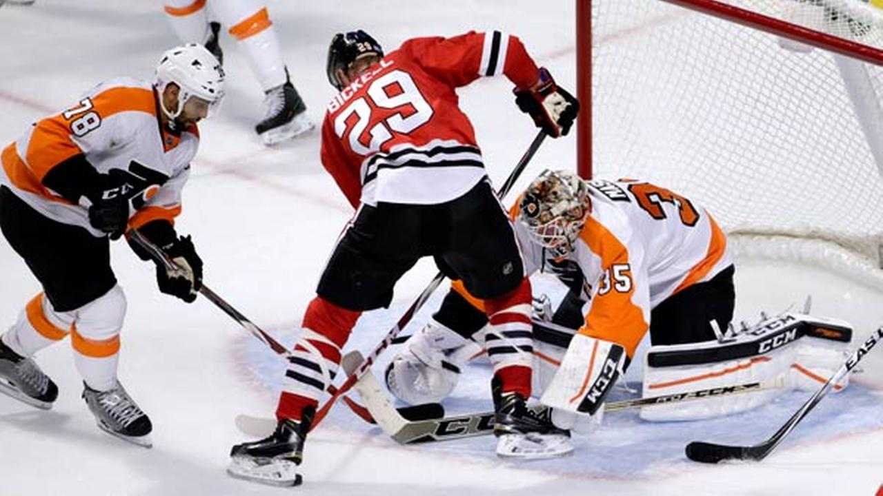 Philadelphia Flyers right wing Pierre-Edouard Bellemare (78) and goalie Steve Mason (35) keep Chicago Blackhawks left wing Bryan Bickell from getting a shot on goal.