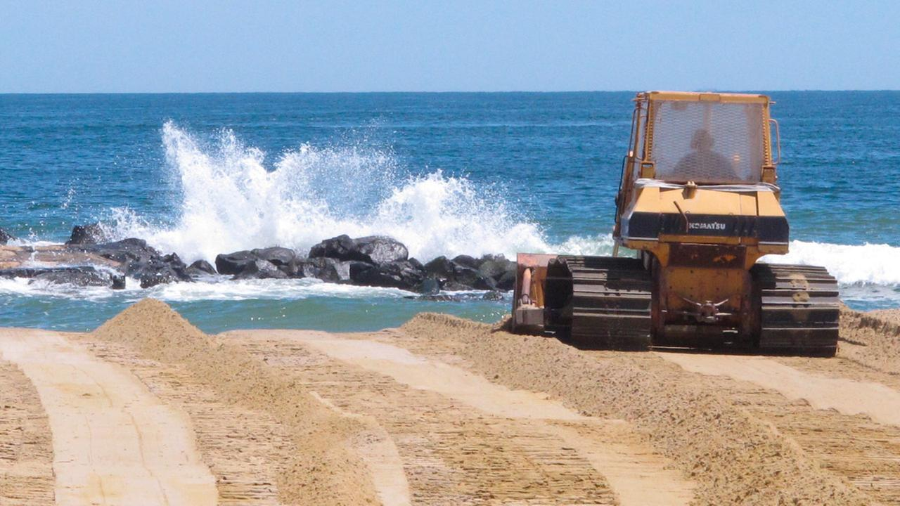 In this May 21, 2018 photo, a bulldozer moves sand on the beach at Spring Lake, N.J. as the New Jersey shore prepares for the start of summer tourism season.