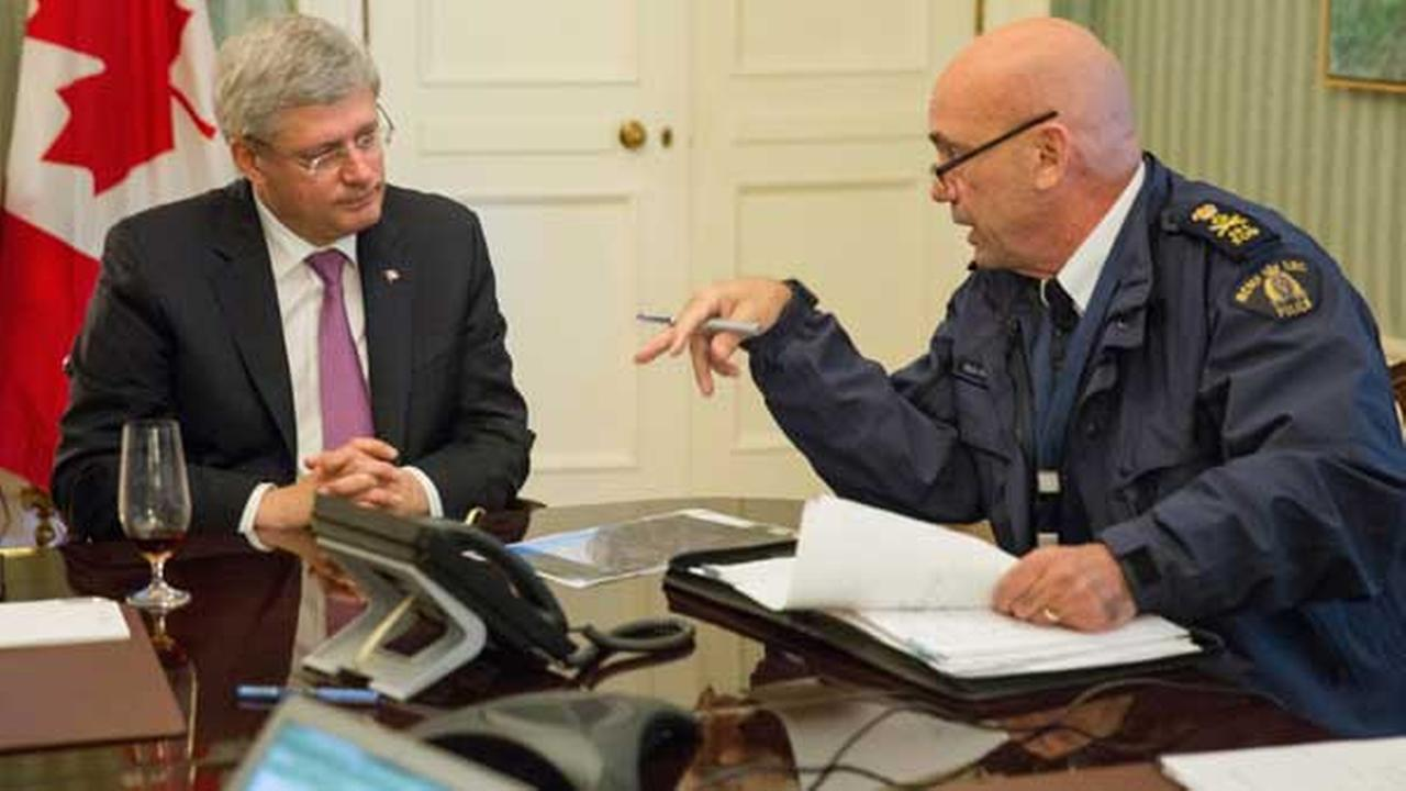 This photo provided by the Prime Ministers office shows the head of RCMP Bob Paulson briefs Canadian prime Minister Stephen Harper on the shootings at Parliament Hill in Ottawa.