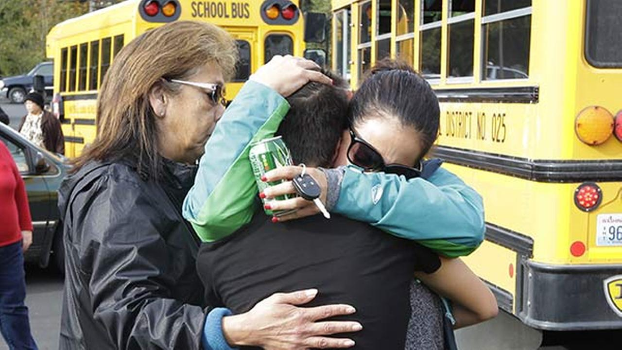 People embrace in front of school buses at a church Friday, Oct. 24, 2014, where students were taken to be reunited with parents following the shooting.