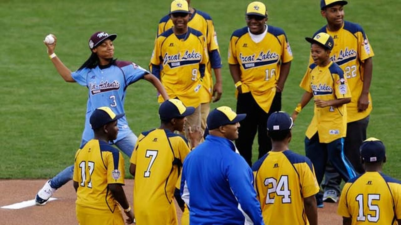 Mone Davis accompanied by players from the Jackie Robison West Little League team, throws out the ceremonial first pitch before Game 4 of baseballs World Series.