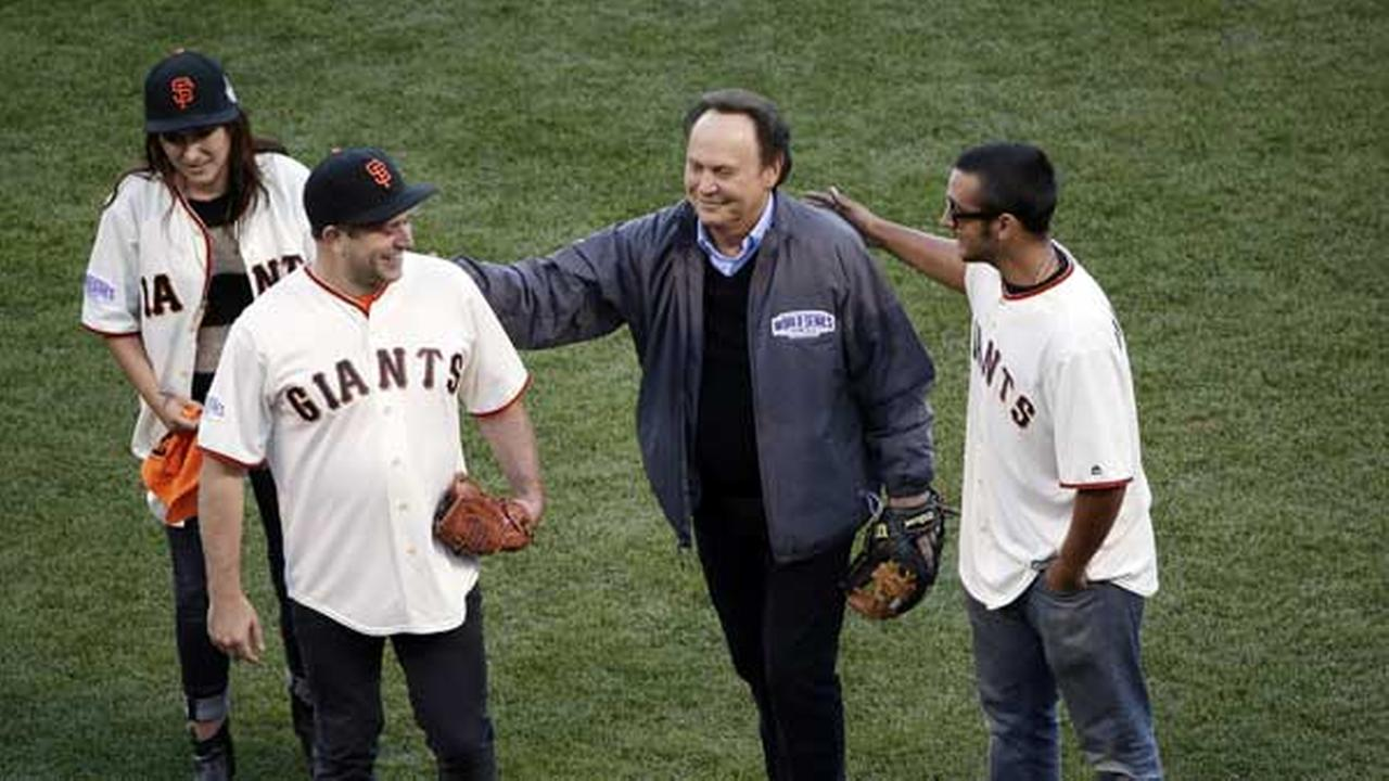 Robin Williams son, Zak Williams, gets a pat on the back from Billy Crystal after Zak threw out the ceremonial first pitch as his siblings Zelda, left, and Cody look on.