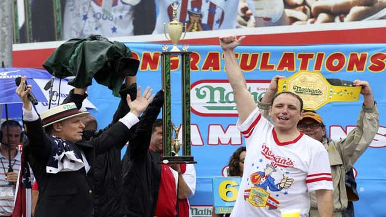 FILE - In this July 4, 2014, file photo, Joey Chestnut raises his fist in the air after winning Nathans Famous Fourth of July International Hot Dog Eating contest at Coney Island.