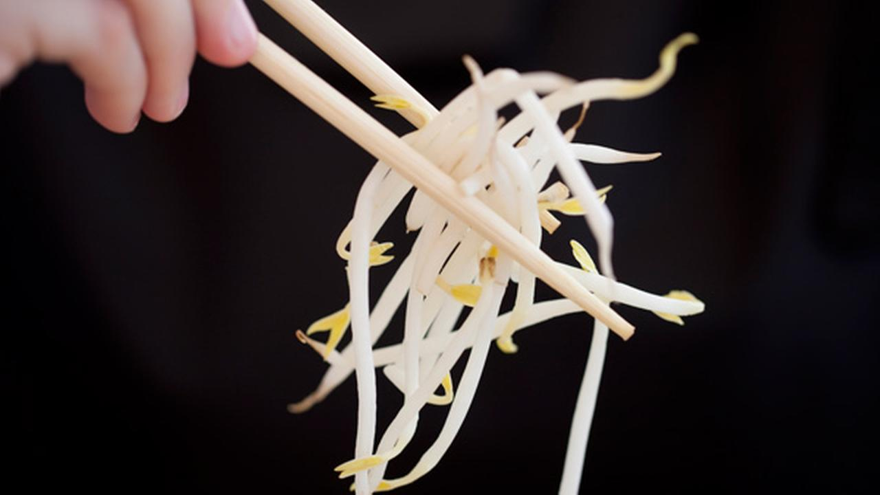 FILE - In this June 5, 2011 file photo, a woman holds bean sprouts with chopsticks in Berlin, Germany. Raw sprouts are again linked to dozens of cases of food poisoning.