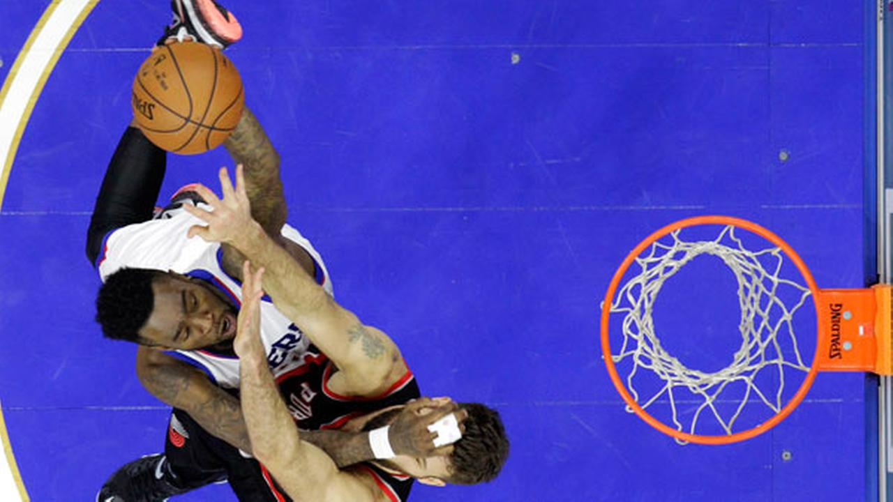 Philadelphia 76ers Tony Wroten, top, goes up for a shot against Portland Trail Blazers Joel Freeland.