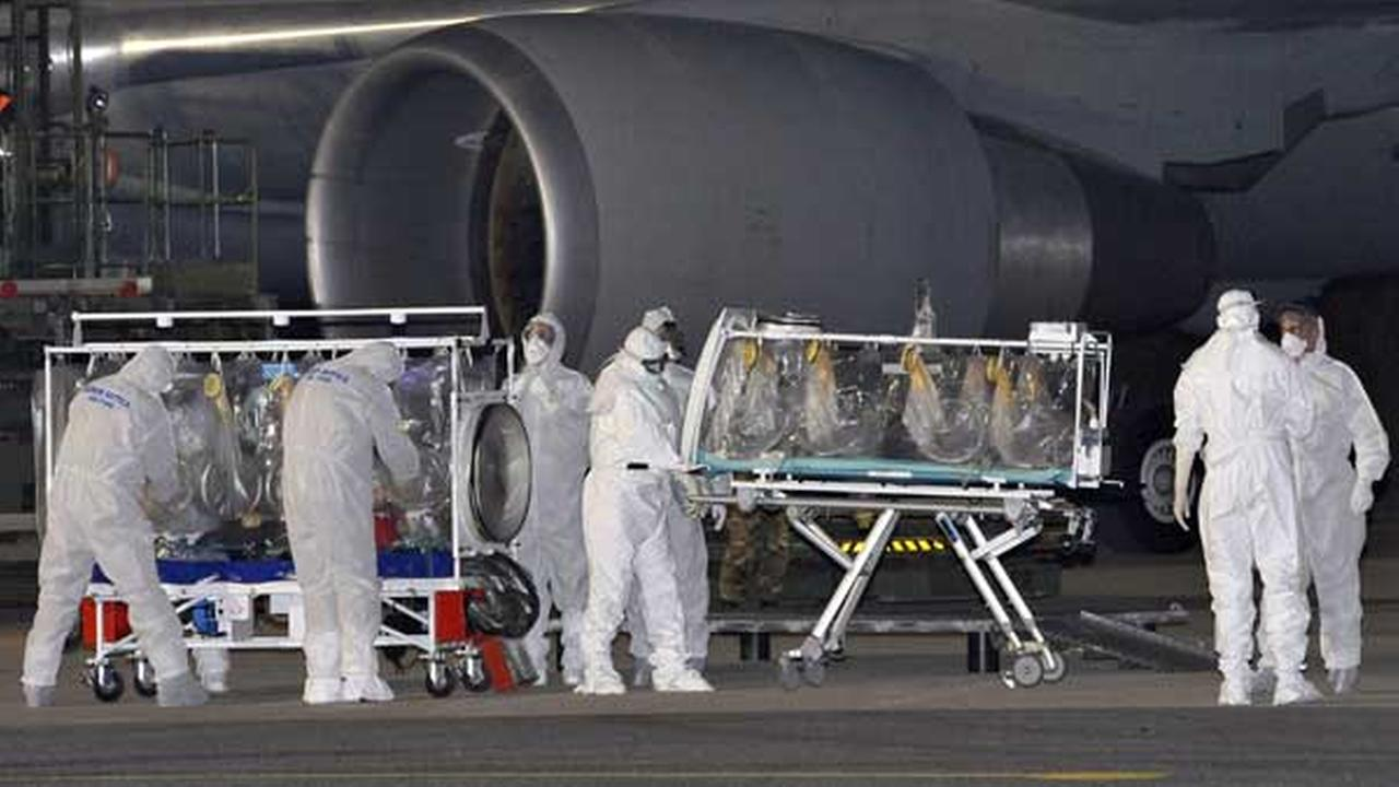 A KC 767 plane is parked on the tarmac as personnel in biohazard suits work by a stretcher encased in a plastic seal carrying a doctor who has tested positive for the Ebola virus.
