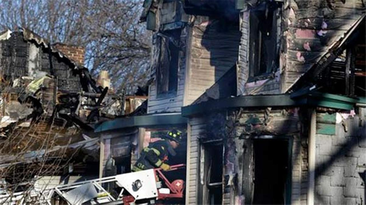 A firefighter searches through the windows of a burned home Sunday, Dec. 7, 2014, in East Orange, N.J.