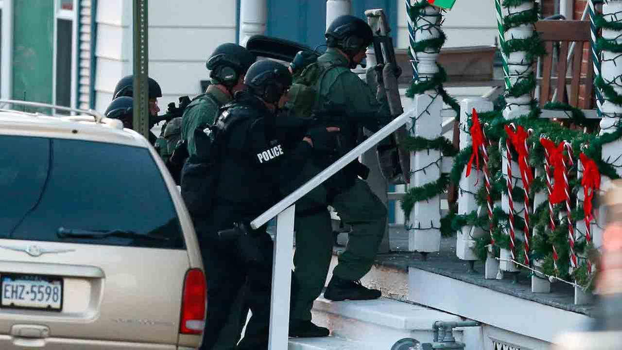 Police gather near a home, Monday, Dec. 15, 2014, in Pennsburg, Pa., where suspect Bradley William Stone was believed to have barricaded himself.