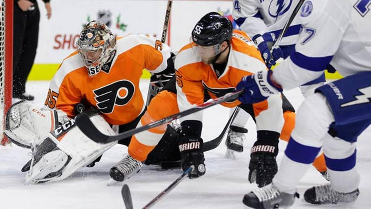 Philadelphia Flyers Steve Mason, left, blocks a shot by Tampa Bay Lightnings Victor Hedman, right, of Sweden, as Nick Schultz looks on.
