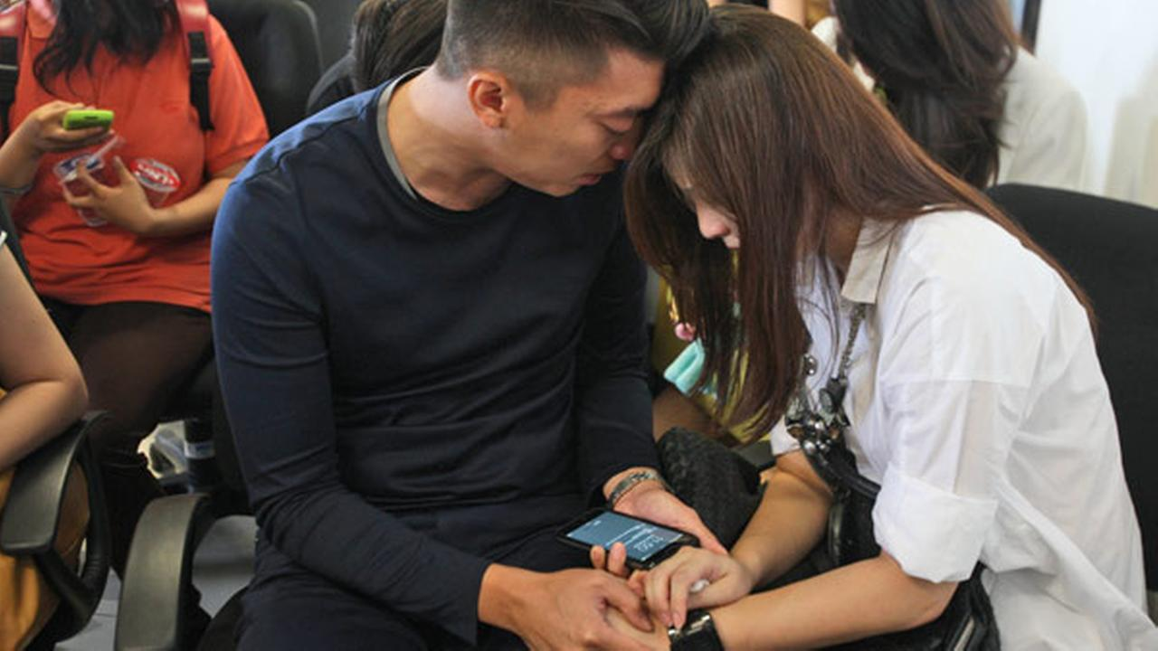 Relatives of the passengers of AirAsia flight QZ8501 comfort each other at Juanda International Airport in Surabaya, East Java, Indonesia, Sunday, Dec. 28, 2014.