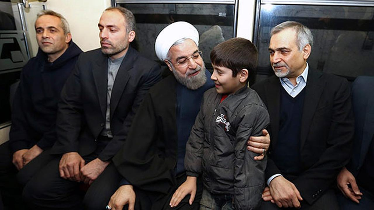 Irans President Hassan Rouhani, center, greets a boy while boarding a subway train in Tehran, Iran, Monday, Jan. 19, 2015. (AP Photo/Iranian Presidency Office, Mohammad Berno)