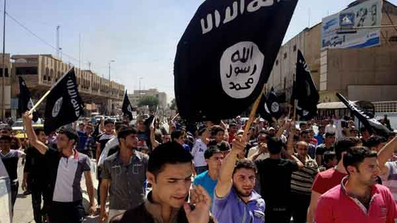 FILE - In this Monday, June 16, 2014 file photo, demonstrators chant pro-Islamic State group slogans as they wave the groups flags.