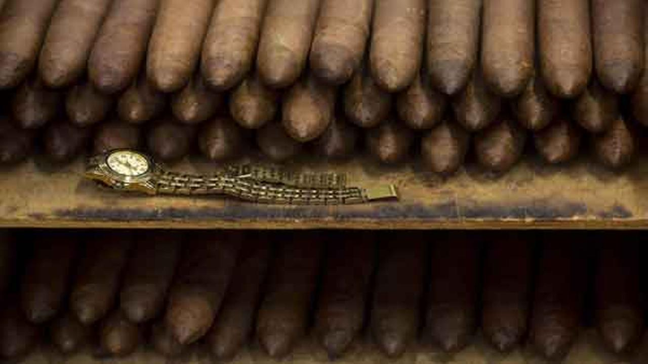 An employees watch sits next to a stack of cigars at the Corona cigar factory in Havana, Cuba, Thursday, Feb. 26, 2015.